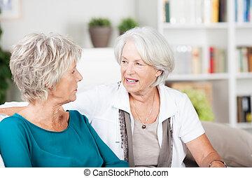 Dos mujeres mayores charlando en la sala