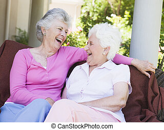 Dos mujeres mayores sentadas al aire libre en una silla
