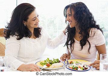 Dos mujeres sentadas en la mesa sonriendo.
