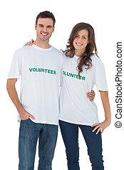 Dos personas alegres usando camisetas voluntarias