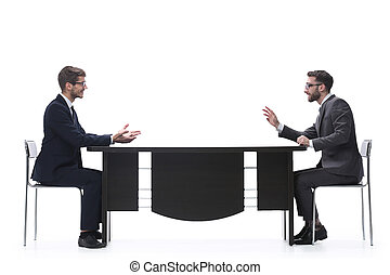 Dos personas de negocios discutiendo algo sentado en la mesa