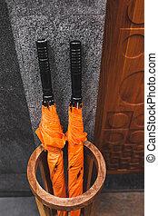 Dos sombrillas naranjas en una canasta de madera afuera