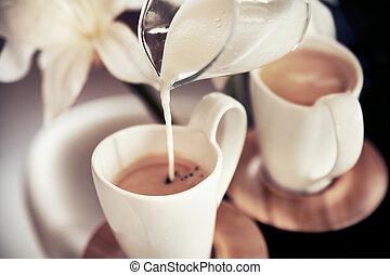 Dos tazas de café con decoración y leche derramada