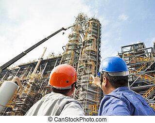 Dos trabajadores de la fábrica discuten y señalan para inspección