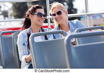 Dos turistas disfrutando de una gira de autobuses en la ciudad