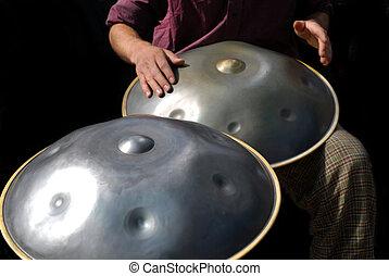 Drummer tocando el tambor de acero colgado con fondo negro