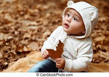 Dulce bebé en el bosque de otoño