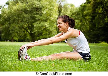 Ejercicio de estiramiento: mujer deportiva al aire libre