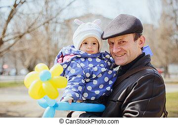 El abuelo sonriente con la niña