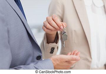 El agente inmobiliario da la llave de la casa