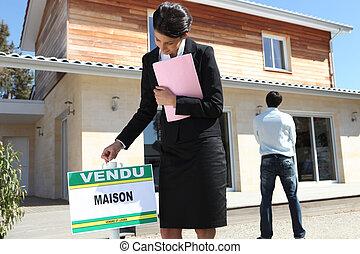 El agente inmobiliario puso una señal de venta frente a una propiedad