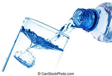 El agua pura se derrama de una botella en un vaso