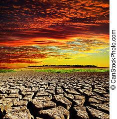 El atardecer rojo y dramático sobre la tierra seca