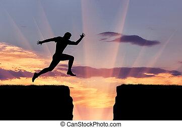 El atleta corredor salta sobre un precipicio