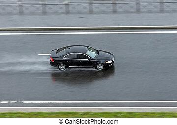 El auto negro va en la lluvia en la autopista.