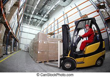 El cargador de Forklift trabajando en Warehous