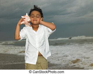 El chico asiático escucha a un conch