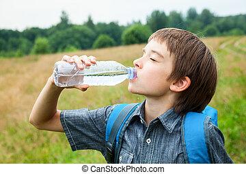 El chico bebe oudoors de agua