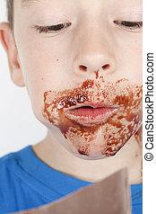 El chico come chocolate delante de un fondo blanco