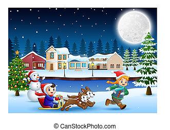 El chico del cartón montando trineo en el pueblo de nieve con un niño corriendo