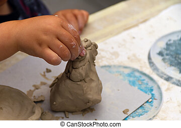El chico haciendo juguetes de arcilla