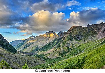 El cielo nocturno con nubes de cúmulos sobre el valle de las montañas