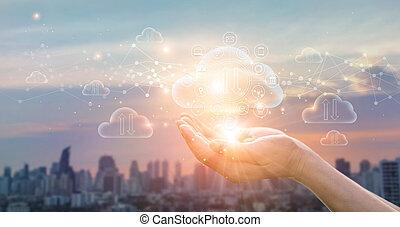 El concepto de computación de nubes. Las manos sosteniendo el intercambio protegido de Data sobre los antecedentes de Sunset City. Conexión de red. Grandes datos y almacenamiento en línea. Tecnología de las nubes