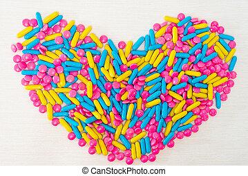 El concepto de salud píldoras coloridas arreglan en forma de corazón aislada