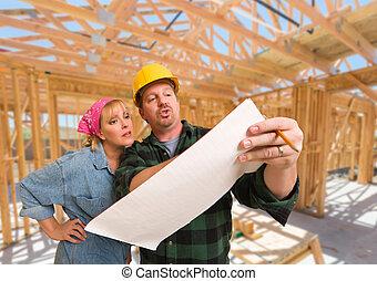 El contratista muestra planes para la mujer en el sitio dentro de la construcción de casas nuevas.