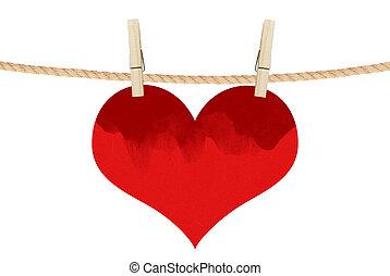 El corazón rojo cuelga de alfileres de ropa aislados en el fondo blanco