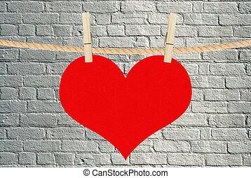El corazón rojo cuelga de alfileres de ropa sobre fondo de ladrillo