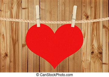 El corazón rojo cuelga de alfileres de ropa sobre fondo de madera