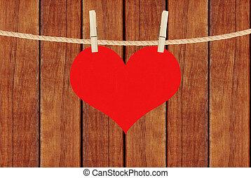 El corazón rojo cuelga de alfileres de ropa sobre los tablones marrones de madera