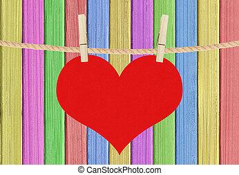 El corazón rojo pende de alfileres sobre el color pintado de madera