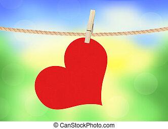El corazón rojo pende de un alfiler sobre el fondo de la naturaleza brillante