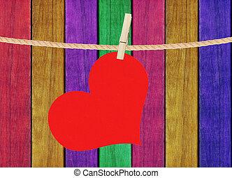 El corazón rojo pende sobre un fondo pintado de madera