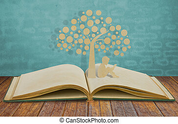 El corte de papel de los niños lee un libro bajo el árbol de un libro viejo