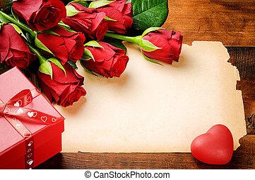 El cuadro de Valentine con rosas rojas y papel antiguo