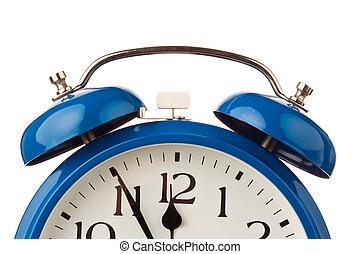 El despertador muestra cinco antes de las doce.