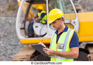 El director de la construcción está escribiendo un informe