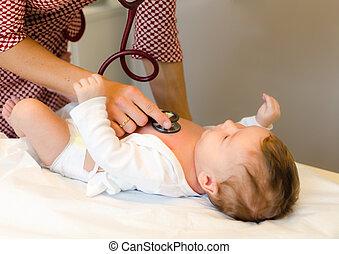 El doctor examina a la niña con estetoscopio