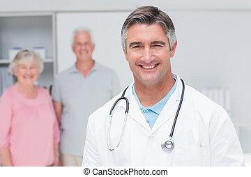 El doctor sonriendo con la pareja de último año en la clínica