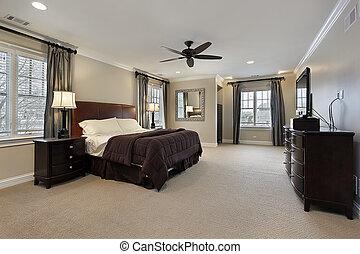 El dormitorio principal con muebles de madera oscura
