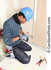 El electricista instalando cables