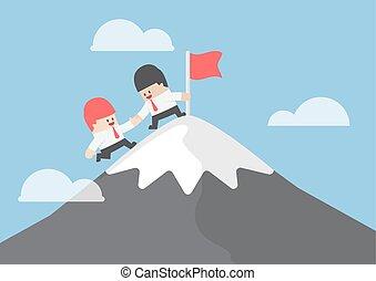 El empresario ayuda a su amigo a llegar a la cima de la montaña