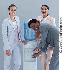 El equipo de negocios bebe de un refrigerador de agua