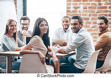El equipo perfecto. Un grupo de seis jóvenes alegres mirando a la cámara con una sonrisa mientras se sientan en la mesa en la oficina