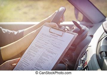 El examinador llena el formulario de prueba de la licencia de conducir