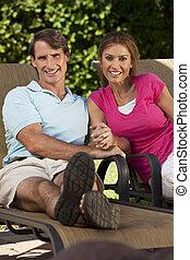 El exitoso y feliz hombre de mediana edad y mujer se toman de la mano