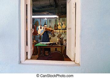 El fabricante de lute comprueba la guitarra clásica en el taller de instrumentos de música